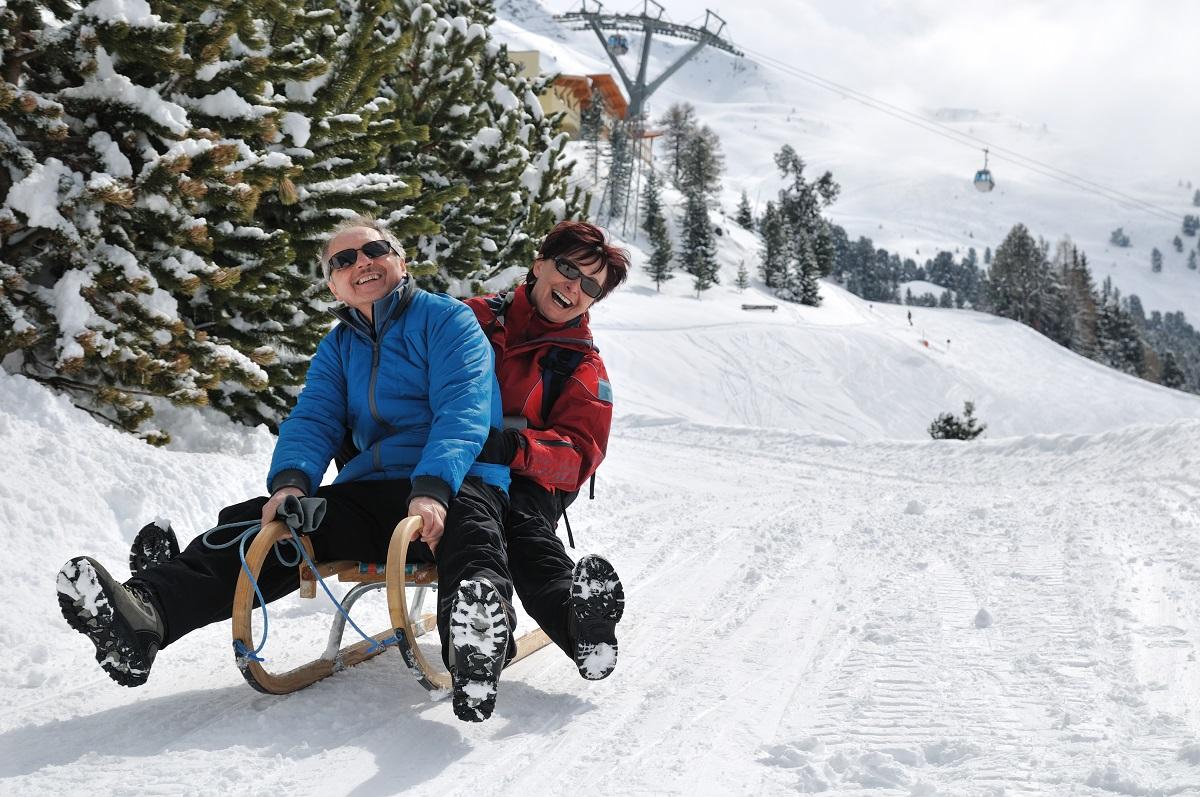 man and woman snow sledding