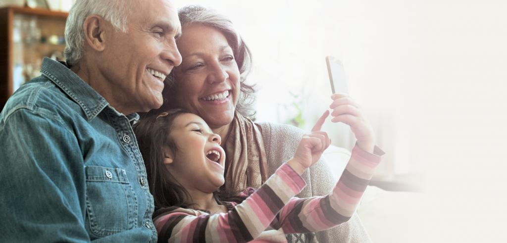 Grandparents with granddaughter on smartphone
