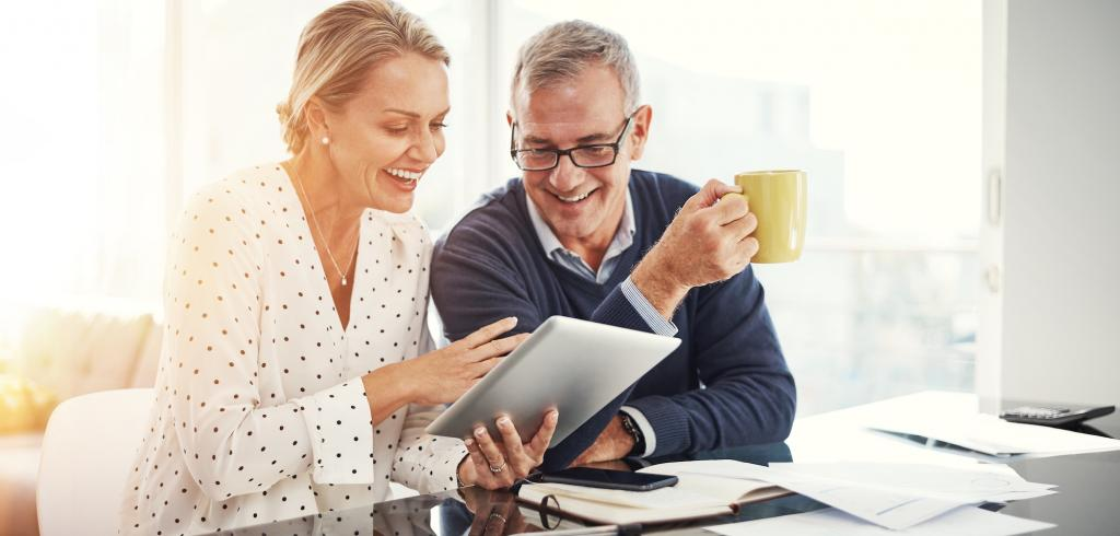 Happy couple reviewing documents on tablet