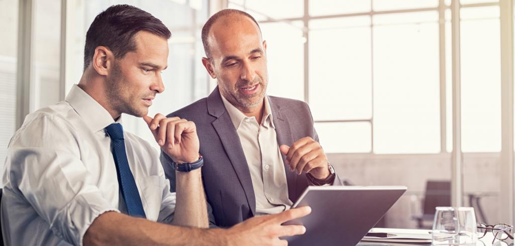 Two business people working on digital tablet
