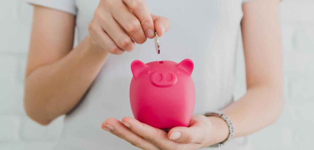 Woman's hand placing coin into piggy bank