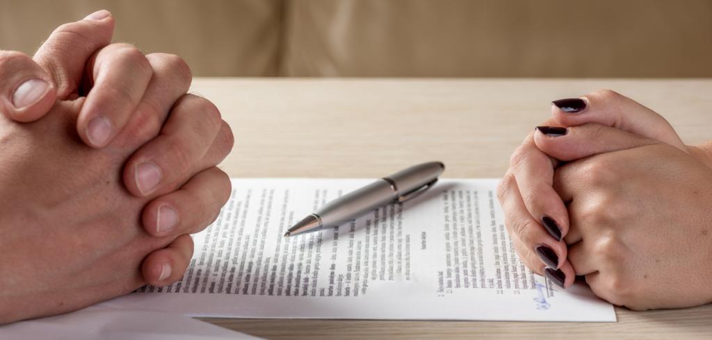 Women and man signing paperwork