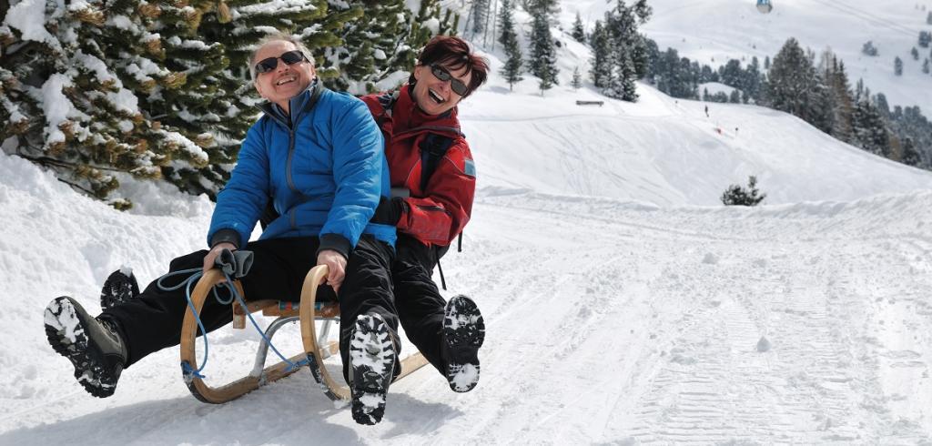 homme et femme sur un traîneau à neige