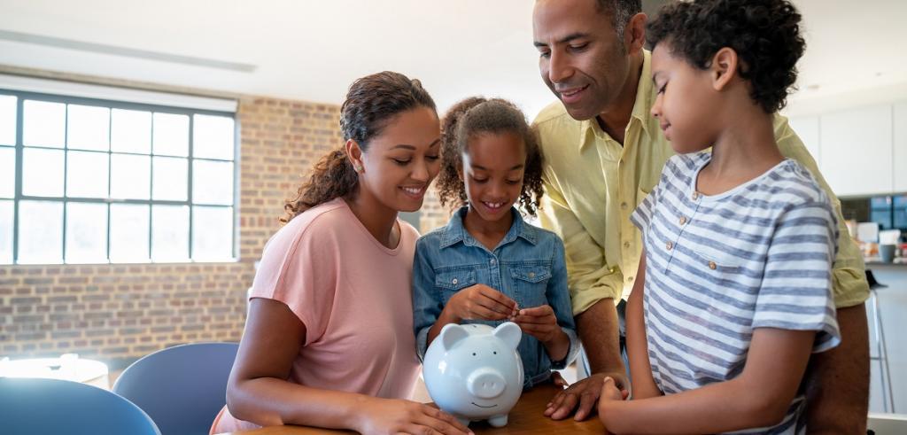 Young family gathering around piggy bank